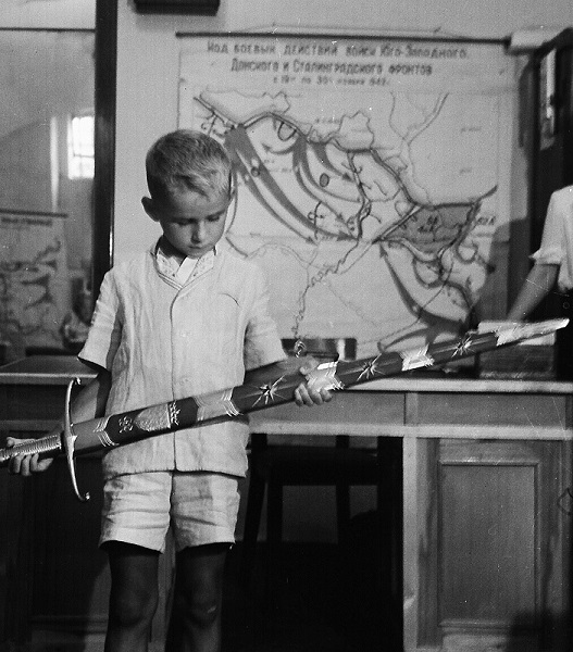 A boy holding the Sword of Stalingrad in 1953